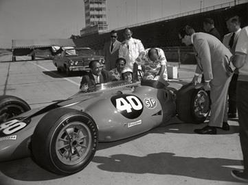 Andy Granatelli, behind cockpit in suit, and his brothers, Vince, left in STP uniform, and Joe, right in STP uniform, help Johnny Carson get comfortable in the STP Turbine in 1967 at the Indianapolis Motor Speedway. Driver Parnelli Jones is behind them in a white firesuit.