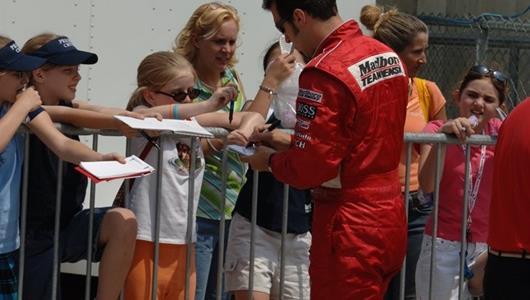 Sam Hornish, Jr., driver for Marlboro Team Penske, signs autographs at the Indianapolis Motor Speedway.