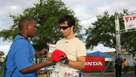 Dale Coyne Racing driver of the #18 Bruno Junqueira signs fans cap.