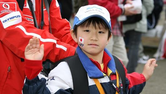 A Hideki Mutoh fan waves to the camera at Twin Ring Motegi in Japan.