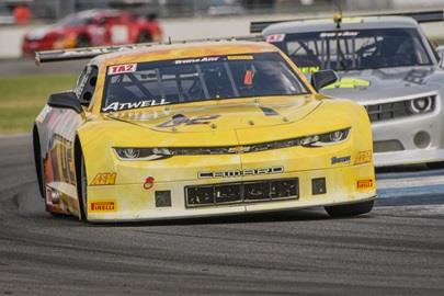Two Camaros hugging a corner on the track at the Brickyard Vintage Racing Invitational