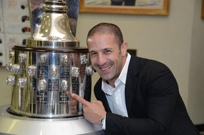 2013 Indy 500 winner Tony Kanaan points to his face on the Borg-Warner trophy