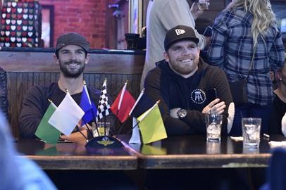 Alexander Rossi and Conor Daly laugh while watching their performance on The Amazing Race as #TeamINDYCAR