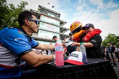 Graham Rahal signs a helmet for a fan and the Firestone Firehawk during the full-field autograph session on Legends Day at the Indianapolis Motor Speedway