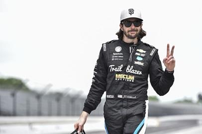 JR Hildebrand throws the peace sign as he walks through the pits during practice for the 102nd Indy 500.