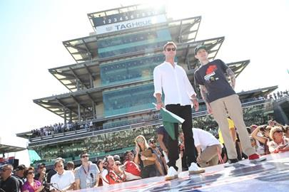 Actor Chris Hemsworth receives the green flag from deadmau5 prior to the start of the Indianapolis 500