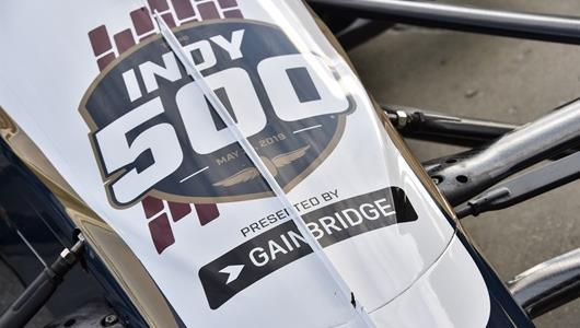 An Indycar branded with the new 103rd Running of the Indianapolis Motor Speedway presented by Gainbridge logo.