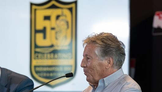 Mario Andretti speaking with a digital image of his 50th anniversary logo.