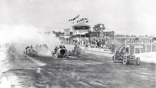 The start of the 300 mile race for the Wheeler-Schebler trophy at the Indianapolis Motor Speedway in 1909, which was the feature race on the last day of a three-day period of automobile racing.