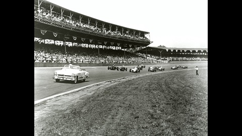 The Chrysler New Yorker V-8 Pace Car leads the 1951 Indianapolis 500 field. The front row, lead by polesitter Duke Nalon in the #18 Novi Purelube with the Kurtis chassis, begins to form up. Lee Wallard, who would win the race, starts second in the No. 99 Belanger Motors Kurtis/Offy.