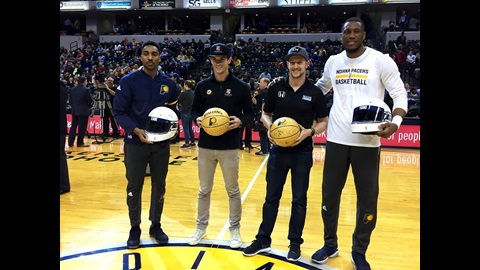 Jeff Teague, Alexander Rossi, Charlie Kimball and Thaddeus Young exchange gifts mid-court before the Indiana Pacers game