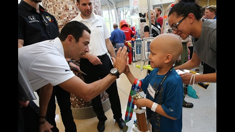 Helio Castroneves 'high fives' a child at Riley Hospital for Children for the #Riley500